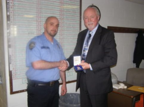 Corrections Officer Peter Ash receives commendation from NH Dept. of Corrections Commissioner, William Wrenn.