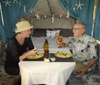 Carolyn and Gordon enjoying dinner in the tiny camper house.