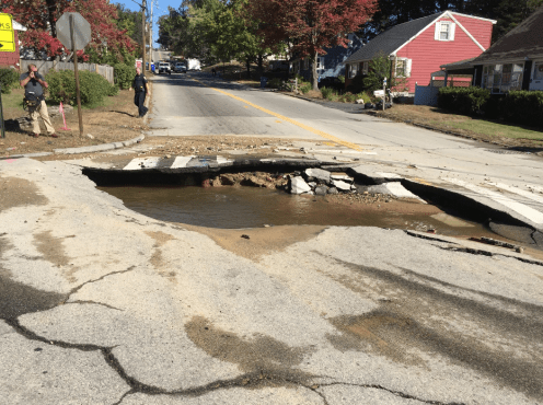 """A portion of a 1955 cast-iron pipe """"blew out"""" causing flooding and road closure."""