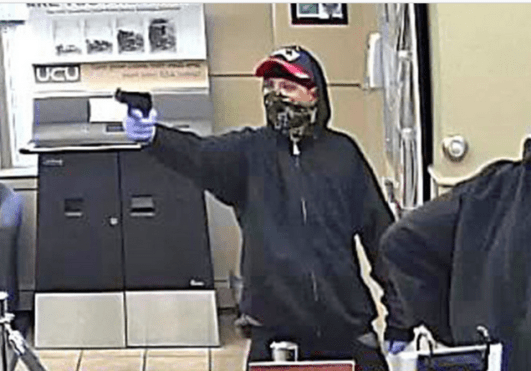 Photo from bank surveillance footage of robber pointing a gun at during Sept. 4 armed robbery at University Credit Union in Portland, Maine.