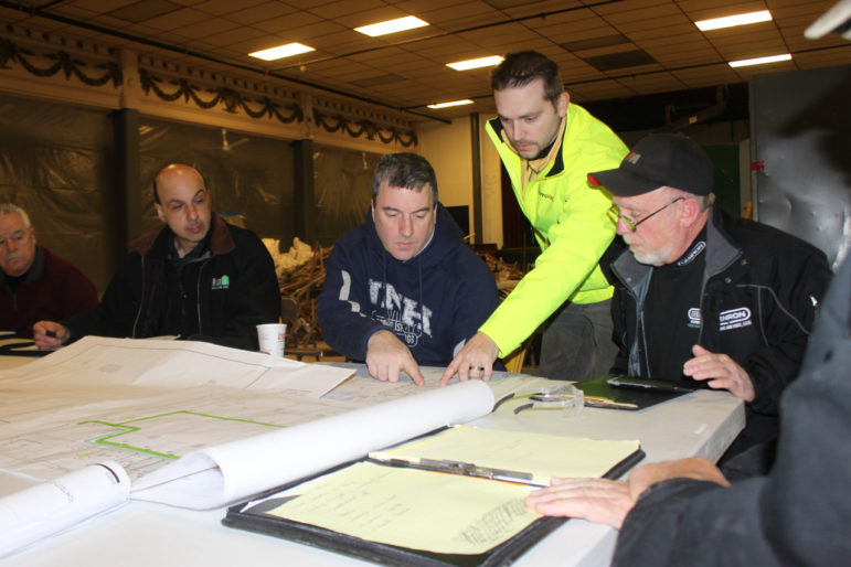 Construction team huddle over the blueprints for the MPAL building renovation.
