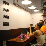 Alexis Dobson reads the plaques on the wall while eating a burger.