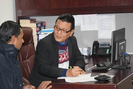 Case Worker Prem Gurung, right, assists a client during a case management meeting.