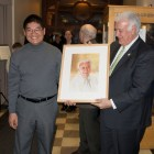 Artist Yong Chen, left, presents a watercolor portrait to Mayor Ted Gatsas.