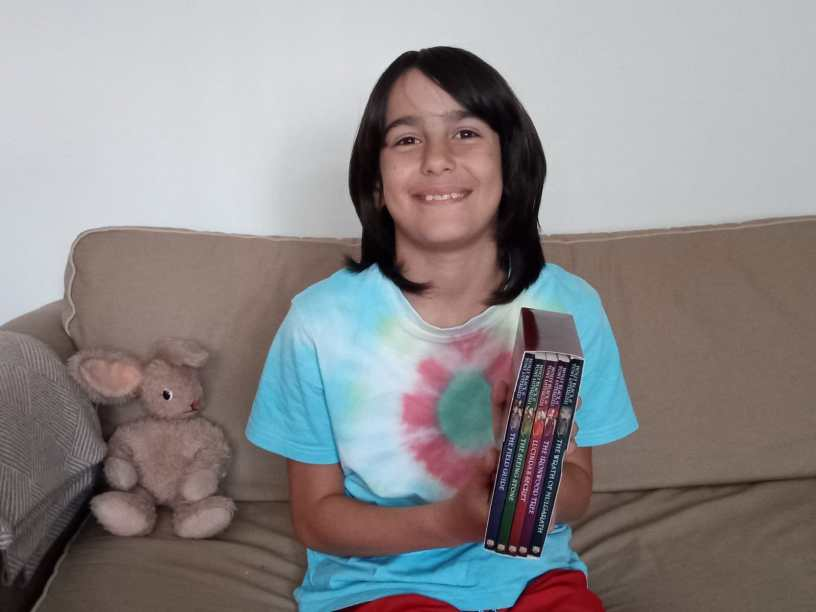 Young boy sat on sofa holding a collection of books.
