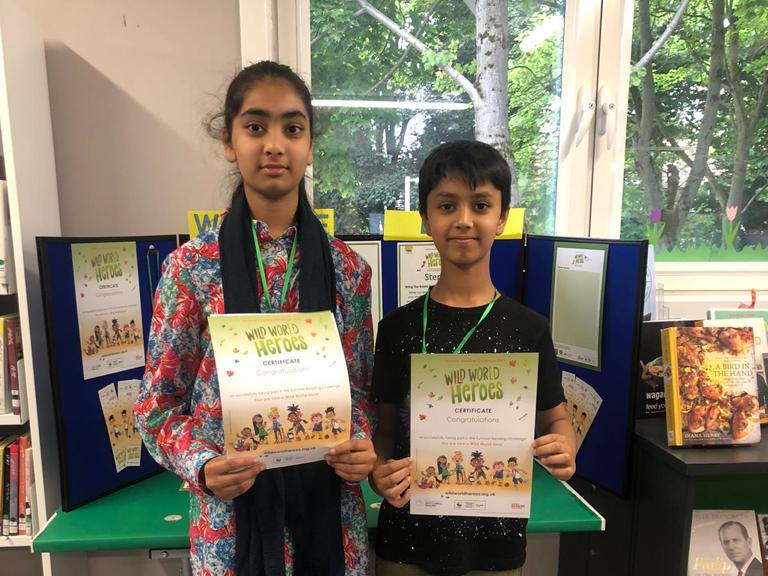 Two children holding wild world heroes certificates