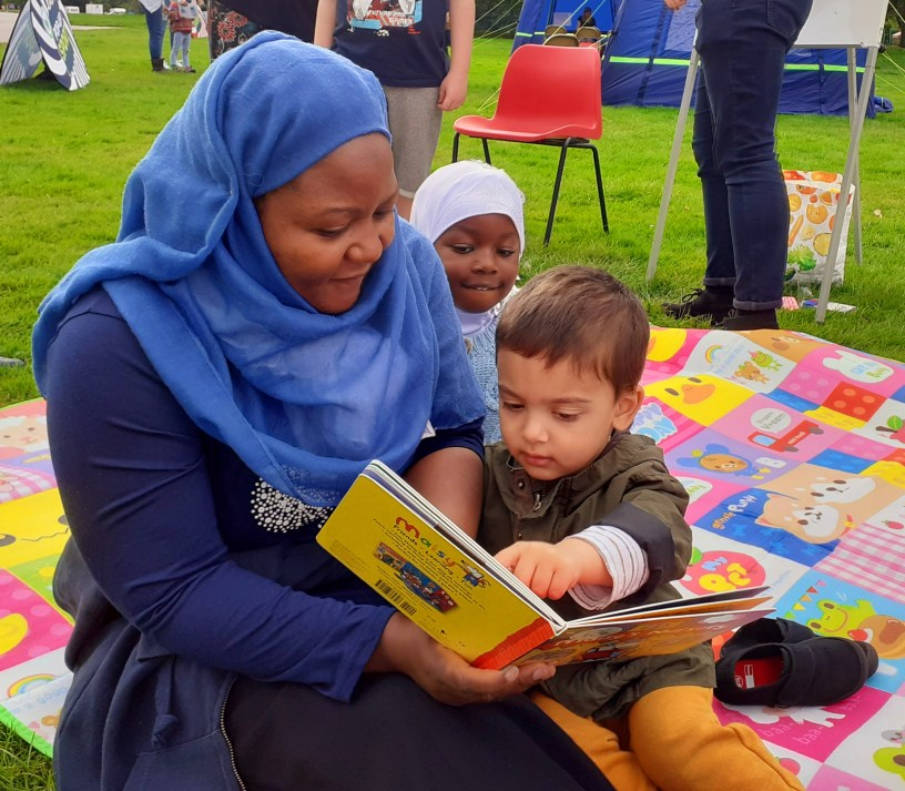 Lady reading book with children whilst sat on a picnic blanket.