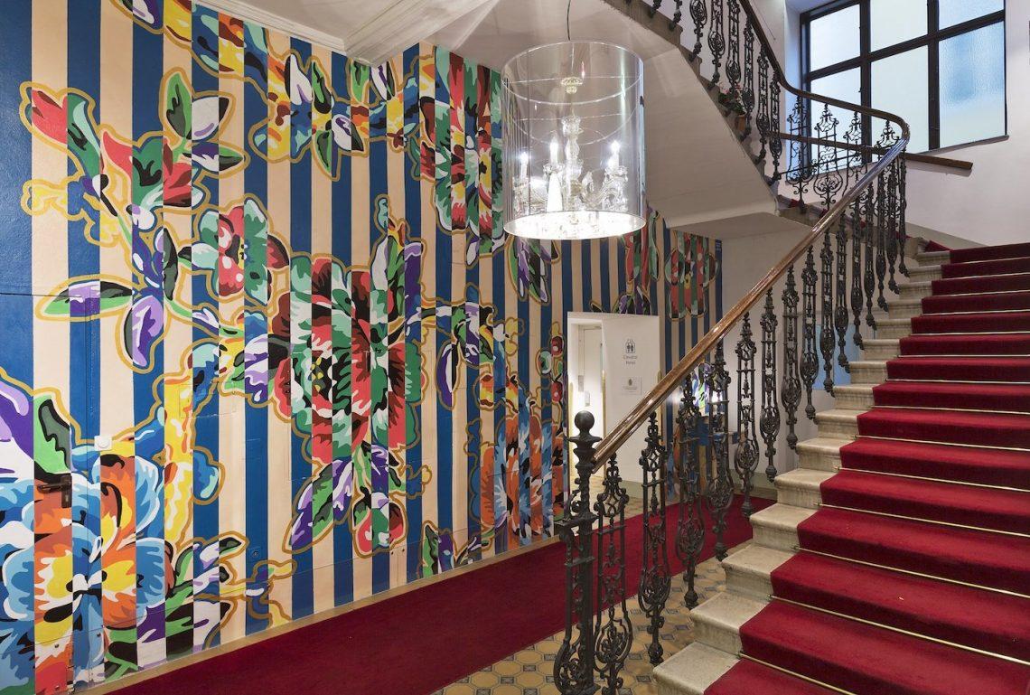 Tapete Muster Deckenlampe Treppe roter Teppich Stufen Geländer Steifen
