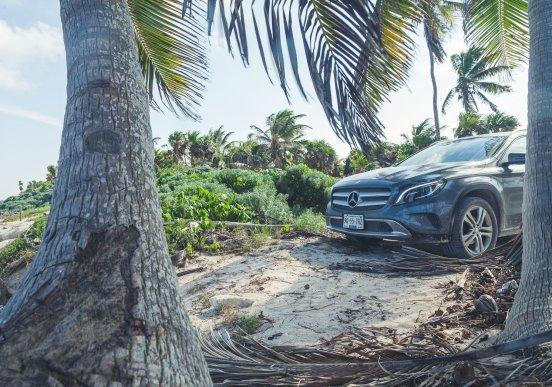 Mercedes-Benz GLA auf Sand zwischen Palmen