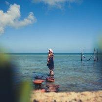 Frau steht im Meer auf Holzbrett