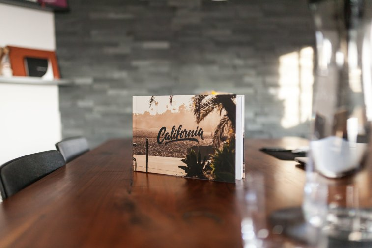 Saal Digital Fotobuch Holztisch Steinwand Stuhl California Palme