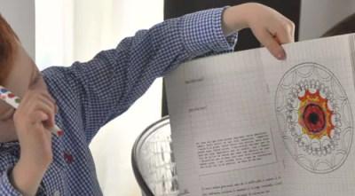 bambino che ha colorato un mandala, incollato su un quaderno