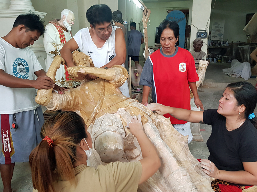 Sanding a wooden Santo statue, Philippines Arts and Crafts