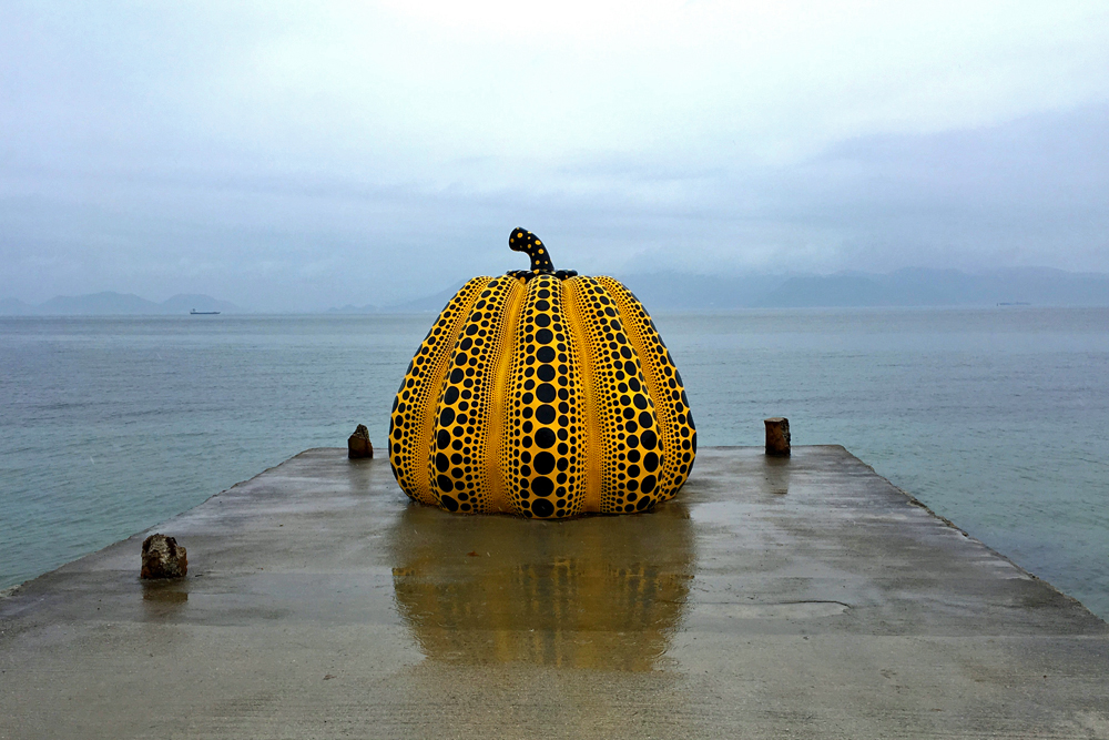 Giant yellow, pumpkin sculpture on a pier on pumpkin Naoshima Island