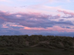 An early spring sunset, reflected in clouds over Southwold beach dunes
