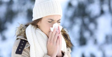 Woman blowing in a tissue in a cold snowy winter