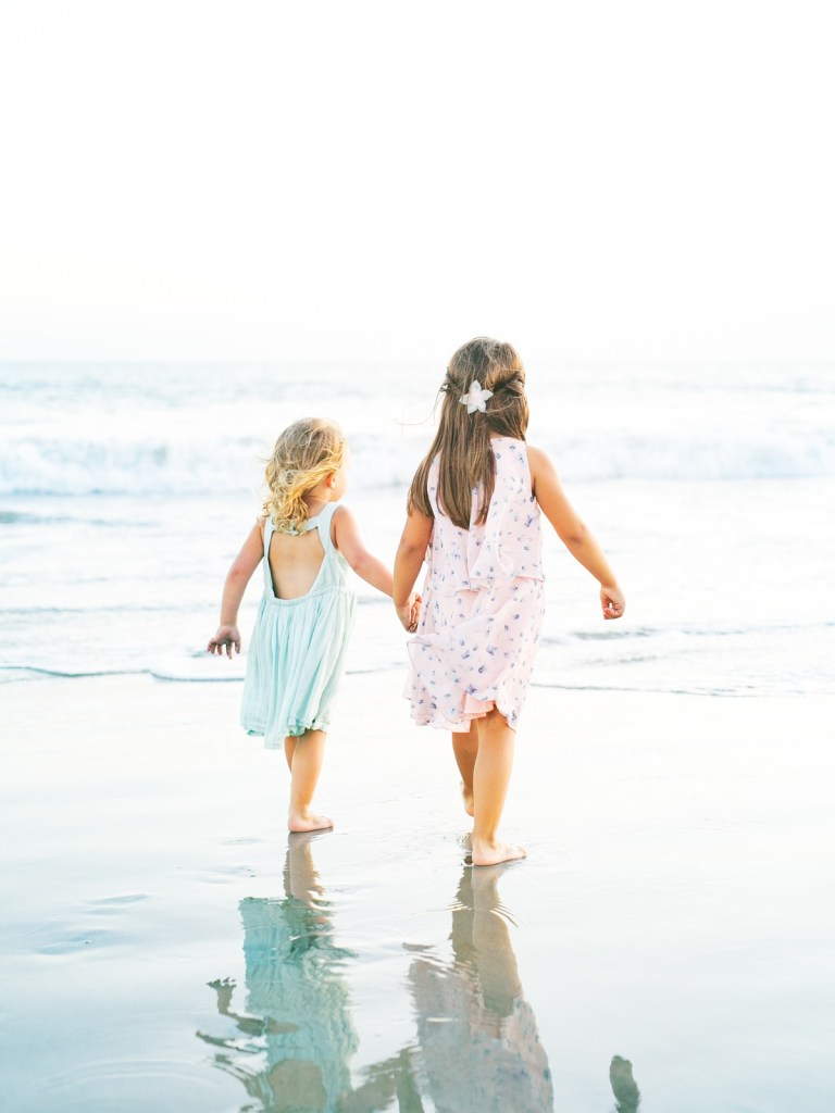 Sisters walking toward the water | | Light and airy Coronado family session shot on film by Mandy Ford