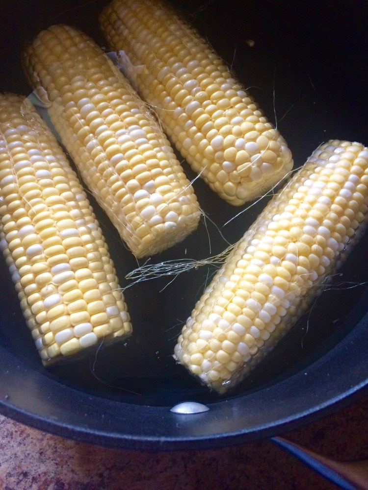 submerge ears of corn in a large pot of water