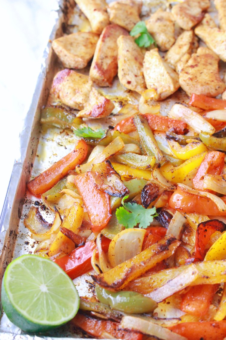 Oven Baked Sheet Pan Chicken Fajitas | Strips of chicken and vegetables are marinated in an easy Mexican marinade and then baked in the oven for an easy, healthy weeknight dinner!
