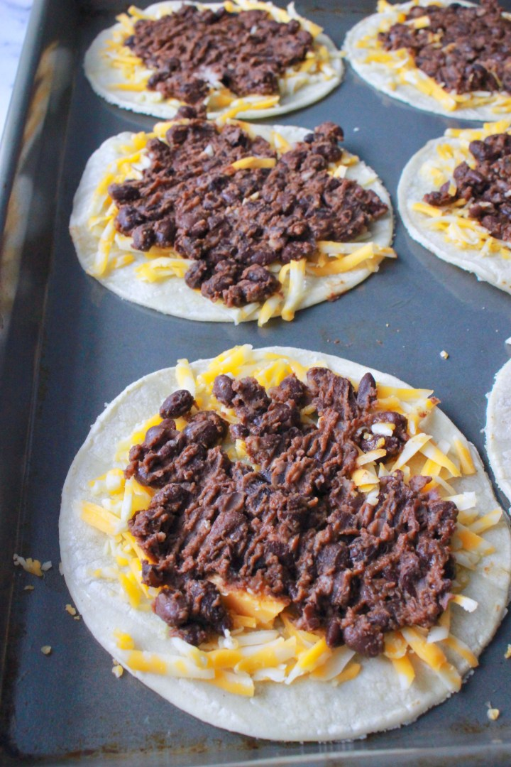 Black Bean Tacos | An easy, healthy, vegetarian tostada that's perfect for Meatless Monday and will get you geared up for Taco Tuesday. Smashed black beans and cheese get baked on a corn tortilla, then slathered in sour cream and topped with homemade corn salsa.