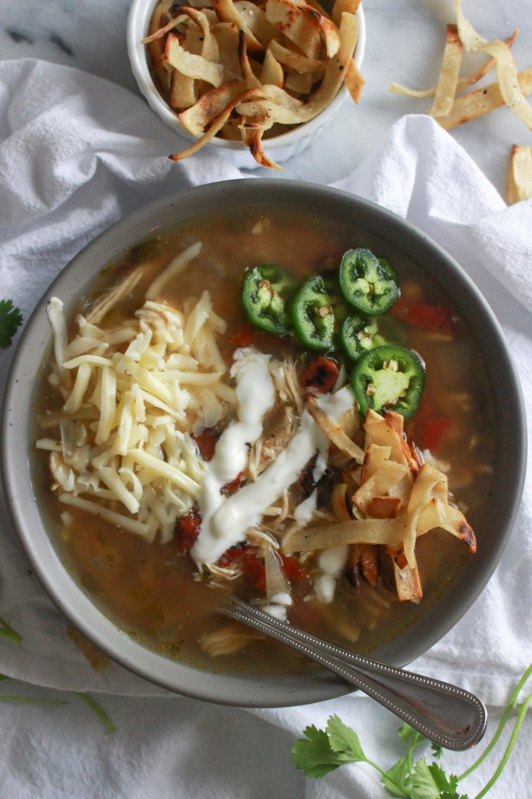 Slow Cooker Chicken Tortilla Soup topped with shredded cheese, jalapeno, tortilla strips, and sour cream