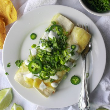 green chicken enchiladas on a plate topped with cilantro, jalapeno, and sour cream