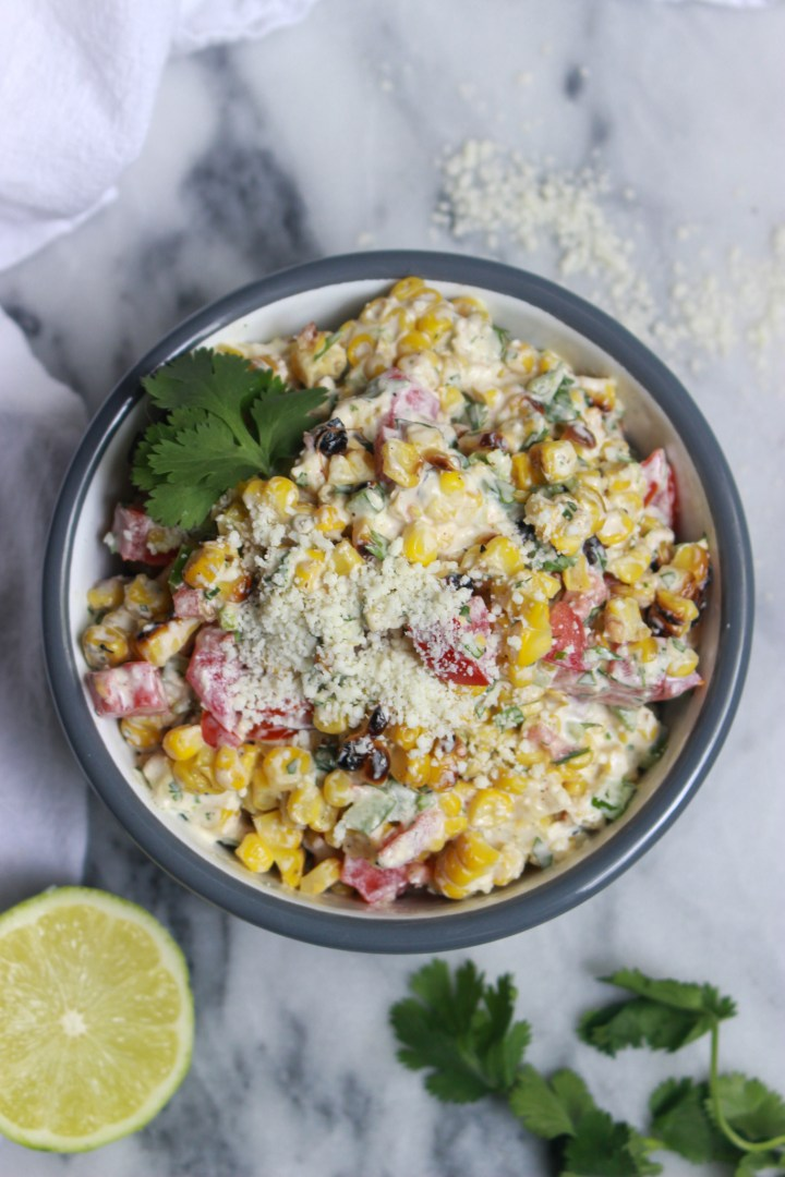bowl of mexican street corn salad with crumbled cotija and cilantro