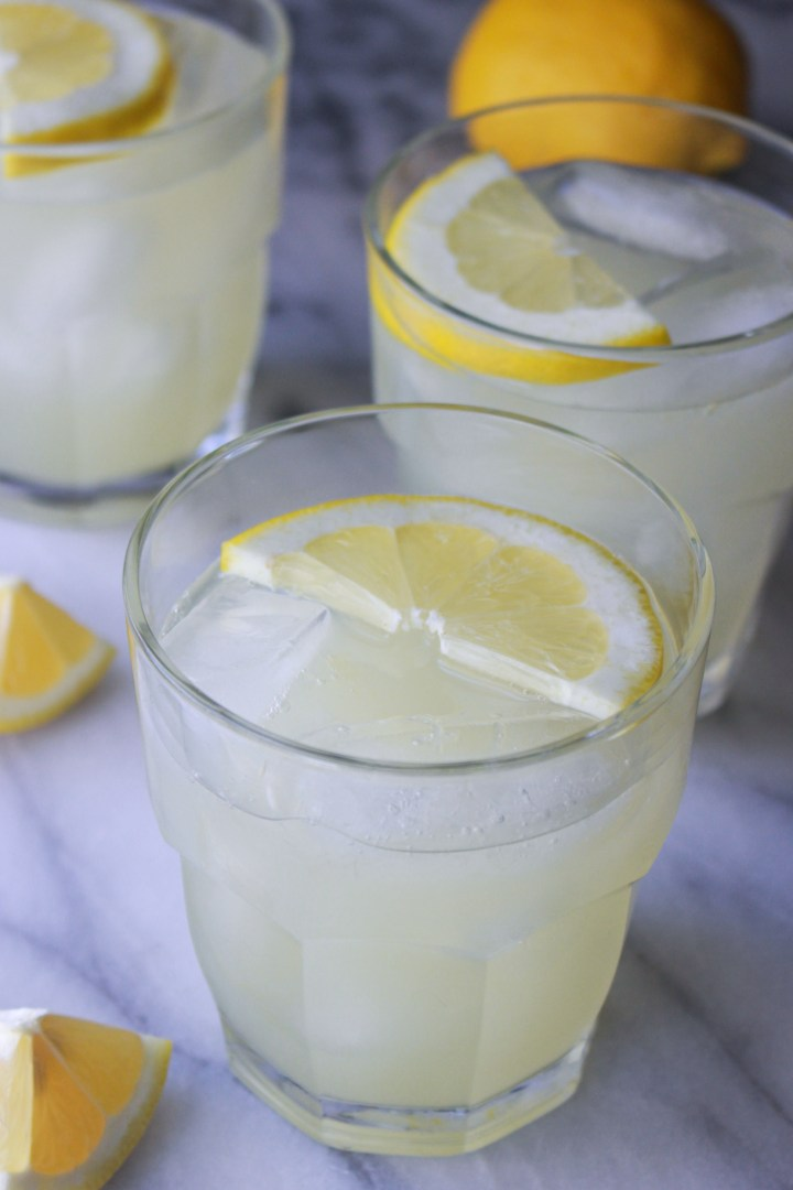 fresh lemonade in glasses with lemon wedges