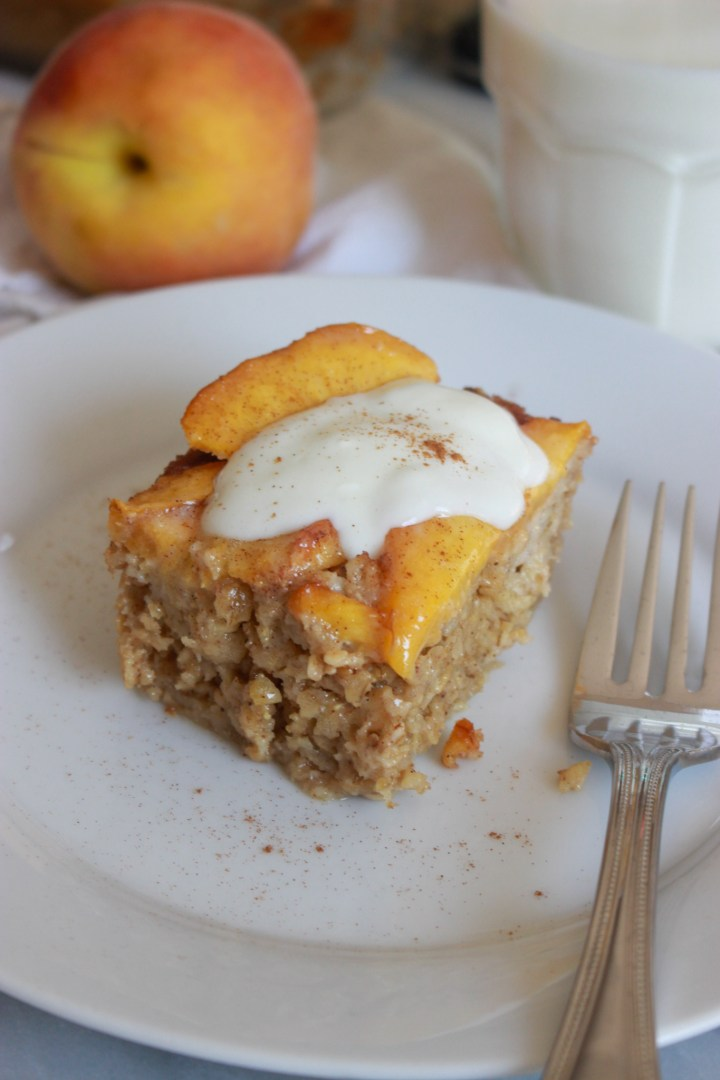 baked oatmeal square topped with peaches and yogurt