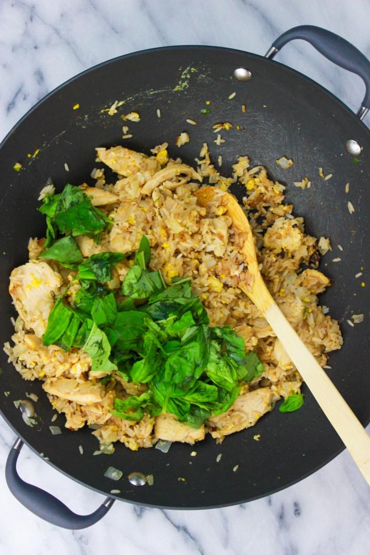 adding basil to wok of thai chicken fried rice
