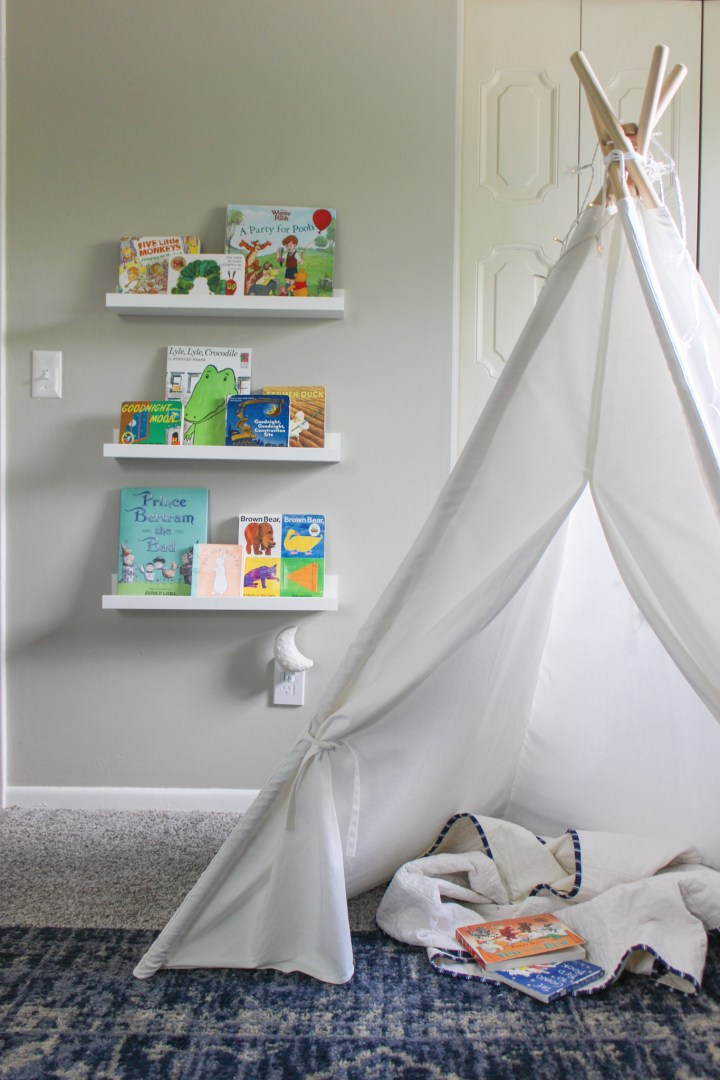 tent for reading with display shelves holding books on wall