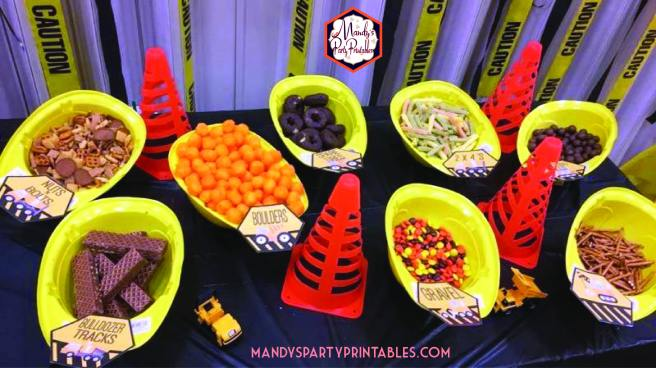 "Food table with upside down hard hats filled with food. Food labels for the food ""Bulldozer Tracks"", ""Boulders"", ""Gravel"" and more 