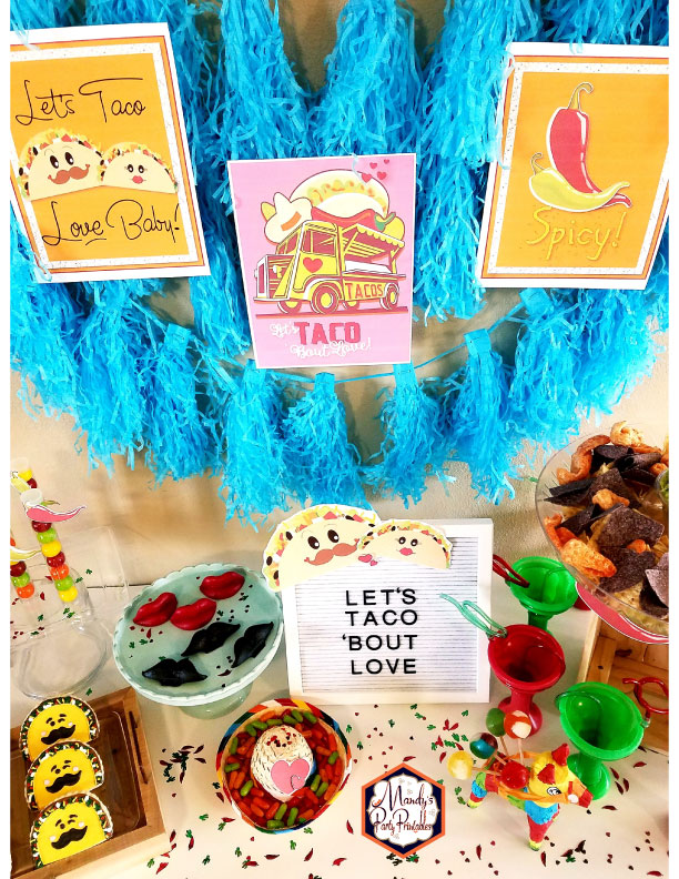 Three party signs on fringed backdrop from a Taco Bout Love Valentine Taco Party | Mandy's Party Printables #valentineparty #tacoparty #tacoboutlove #ilovetacos #MPP #fiesta