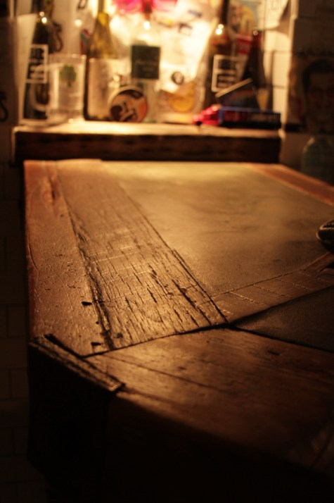 Reclaimed lumber and artisanal concrete bar surface.