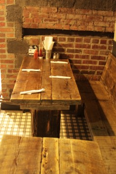 Restaurant tables (rectangular tops) and bench, all made from reclaimed woods. Half-booth seating.