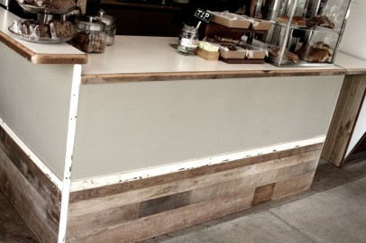 Sage green formica counter with reclaimed wood details.
