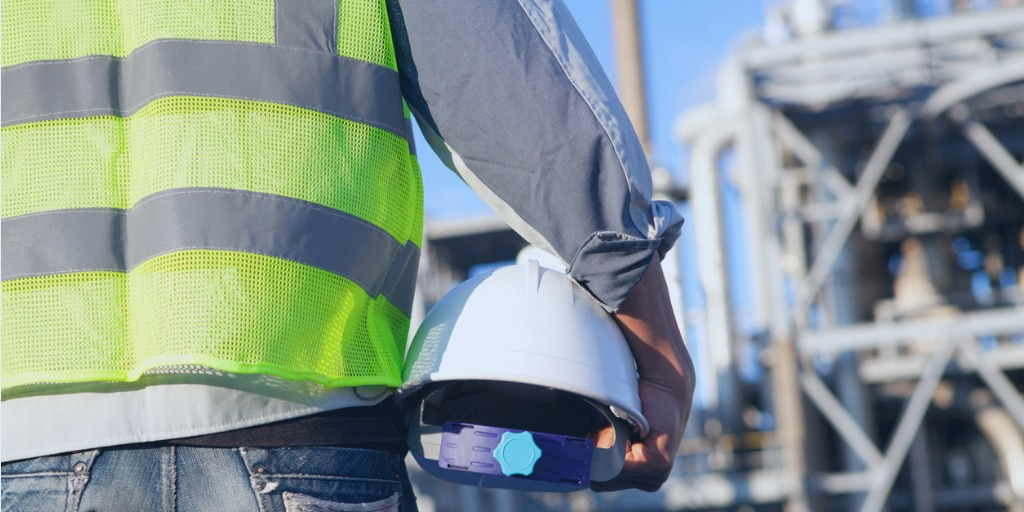 Promoting a sustainable process safety culture. Engineer holding a hard hat with a refinery in the background