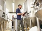 men with clipboard at craft brewery or beer plant