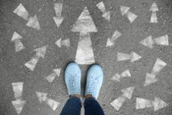stock-photo-woman-standing-on-asphalt-road-with-arrows-pointing-in-different-directions-concept-of-choice-1200387280.jpg