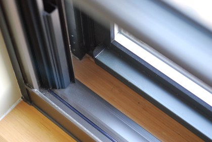 A grey soundproof piece of tape was applied to a wooden window sill to dampen the noise allowed through.