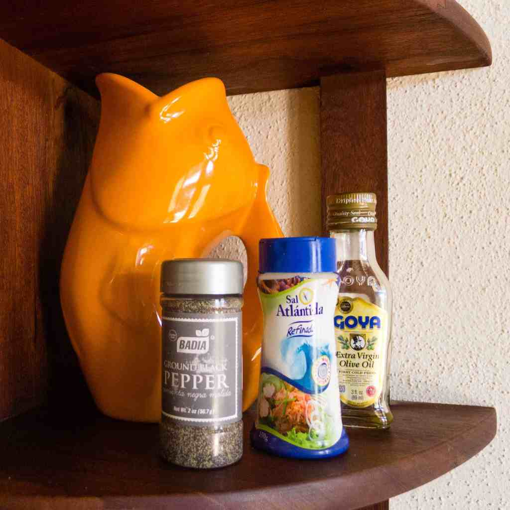 Salt shaker, pepper shaker and a small bottle of olive oil.
