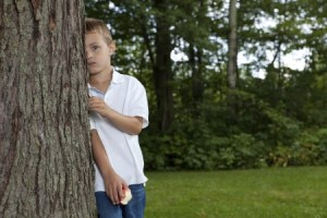 shyness and social anxiety boy behind tree