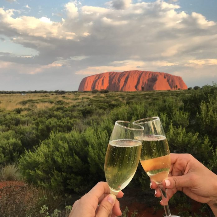 A champagne toast while watching the sunset over Uluru is a highlight of Adventure Tours' Rock to Rock Tour.