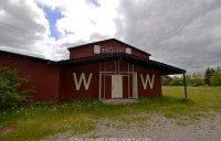 A red wooden country dance hall called Wheelers under cloud and sun. Outside Stephenville, Newfoundland.