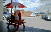 Looking out from the window of a cafe in , Newfoundland. Condiments sit on a mini picnic table in the window, while traffic passes by.