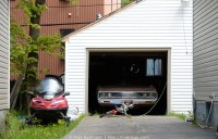 Three modes of transportation in a driveway: a snowmobile to the left, an old Dodge Dart in a garage, and a child's bike. Corner Brook, Newfoundland.