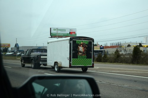 A pickup truck pulls a trailer with the logo of the Poizon Whiskey Band down the highway on a cloudy day