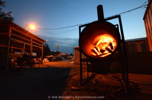 Behind a Kentucky barbecue restauarant at night, Flames shoot upward from a burning pile of hickory logs in a steel tube