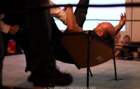 A wrestler is thrown back-first through a cheap folding table, splitting it in half