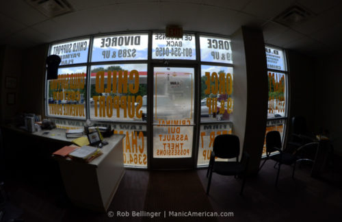 Interior view of a law office within a gas station, looking through windows covered with advertisements for divorce and child support work